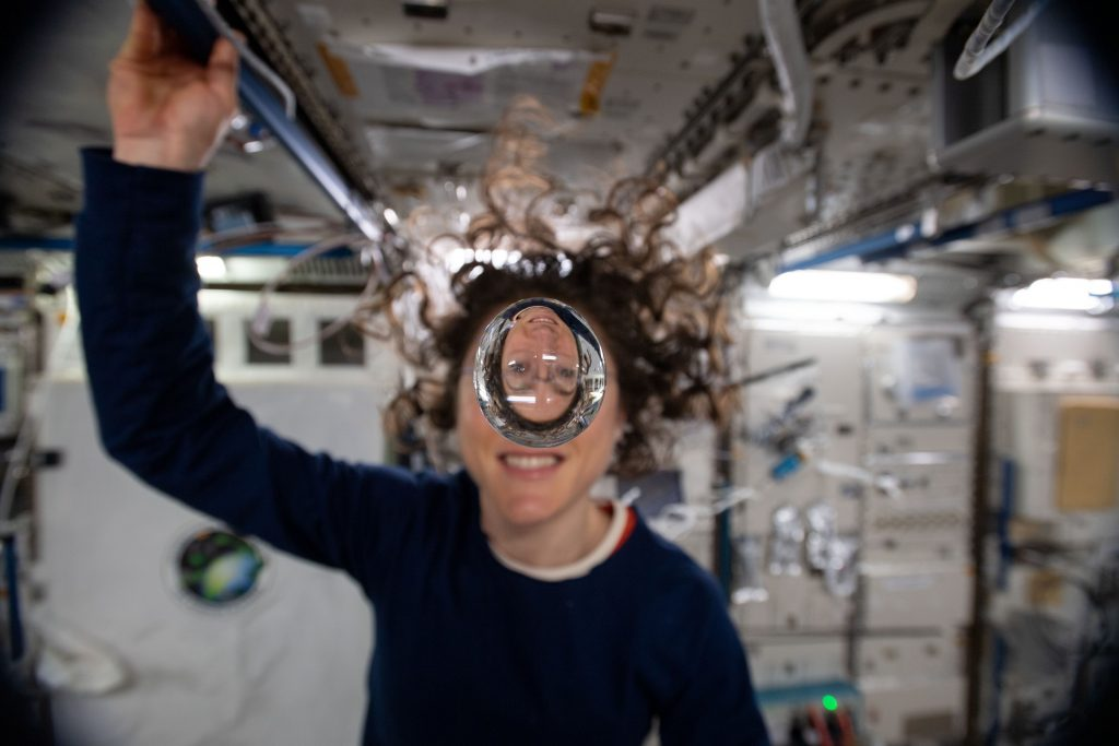 Expedition 60 Flight Engineer Christina Koch of NASA playfully demonstrates how fluids behave in the weightless environment of microgravity aboard the International Space Station.