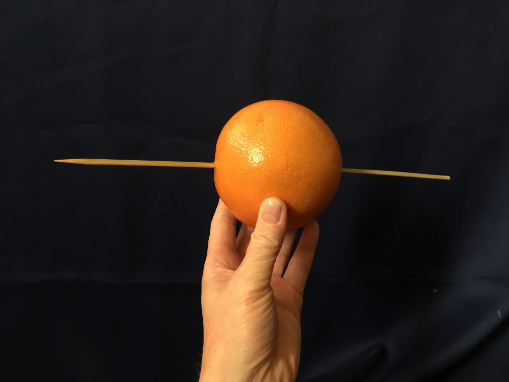 Step 1: push the skewer through the orange to make the Earth's axis
